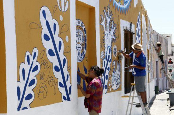 """ACOMPAÑA CRÓNICA: MÉXICO ARTE MEX07. XANENETLA (MÉXICO), 02/04/2016.- Fotografía del 31 de marzo de 2016 de artistas Colectivo Tomate pintando un mural en el barrio de Xanenetla en la ciudad de Puebla (México). El barrio de Xanenetla, considerado como uno de los más """"bravos"""" de la ciudad de Puebla (centro de México), ha sido por años epicentro de crímenes y delitos; sin embargo, la colina ha sufrido una transformación gracias al arte. EFE/Francisco Guasco"""